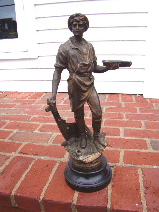 click to view larger image of A 19th century metal sculpture of a shipbuilder holding a small ship in one hand and his tool in the other. Circa 1883.