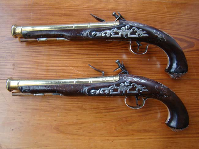 click to view larger image of A rare pair of English  Naval Officers' flintlock pistols with brass cannon blunderbuss barrels and silver mounts by William Grice of Birmingham circa 1770