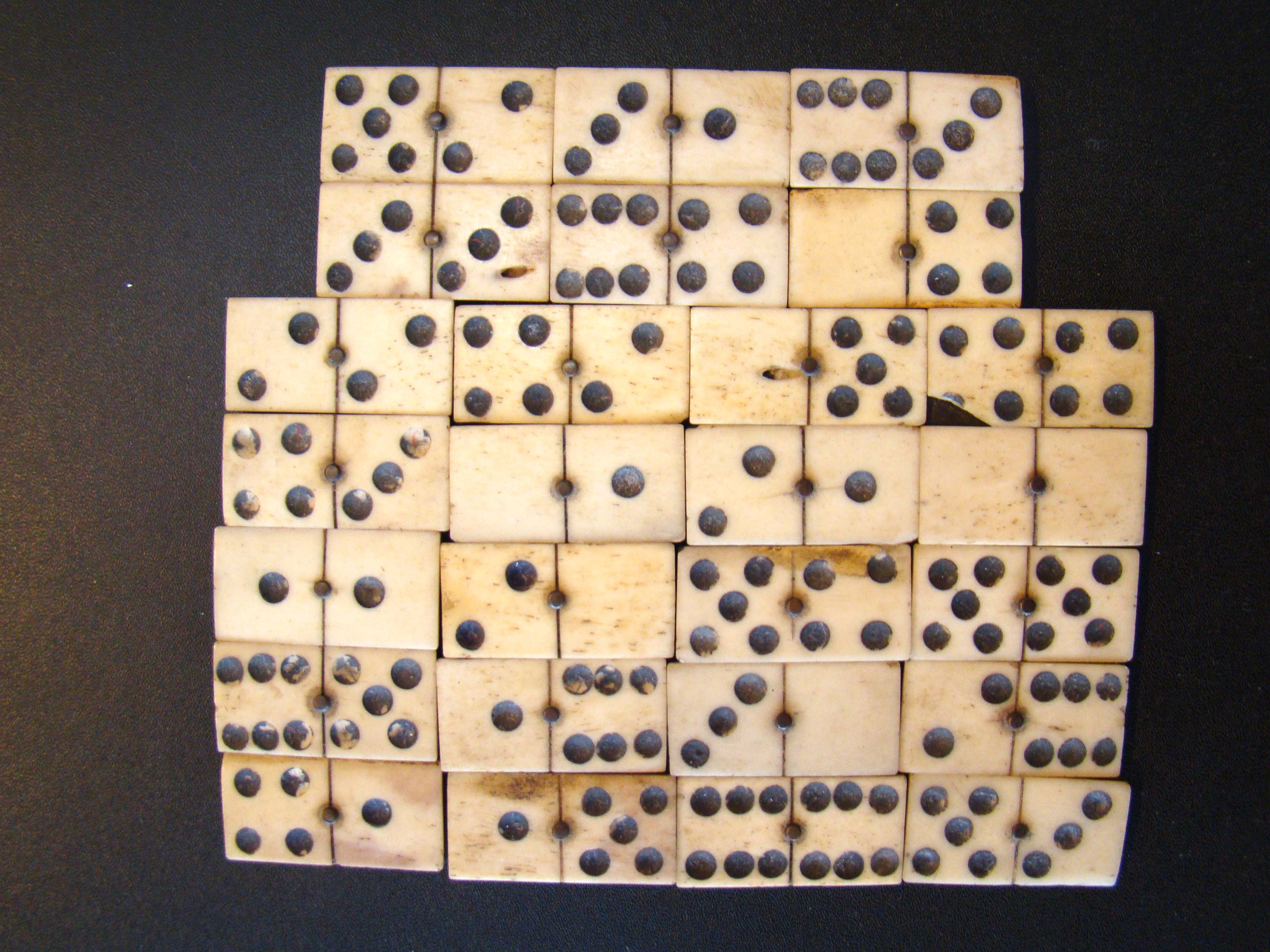 click to view larger image of A group of 26 hand-cut bone and ebony dominoes circa 1865