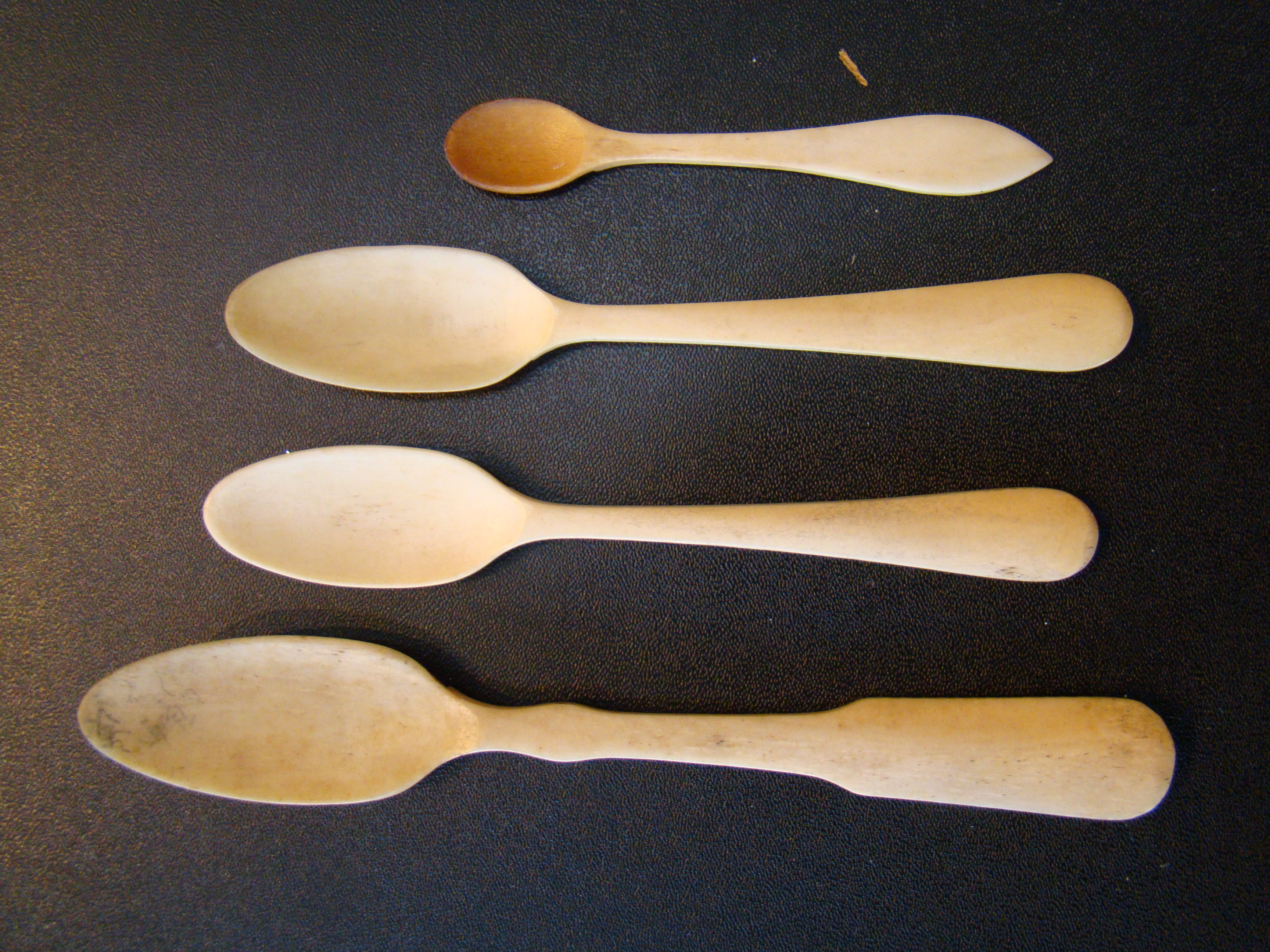 click to view larger image of A group of four 19th century sailor-made whalebone spoons
