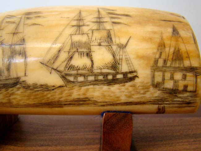 click to view larger image of A 19th century Scrimshawed Whale's Tooth depicting a ship firing at an American fort and the fort firing back with its' cannons.