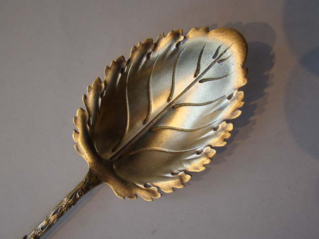 click to view larger image of An unusual 19th century silver gilt serving spoon in the form of a branch and a leaf.