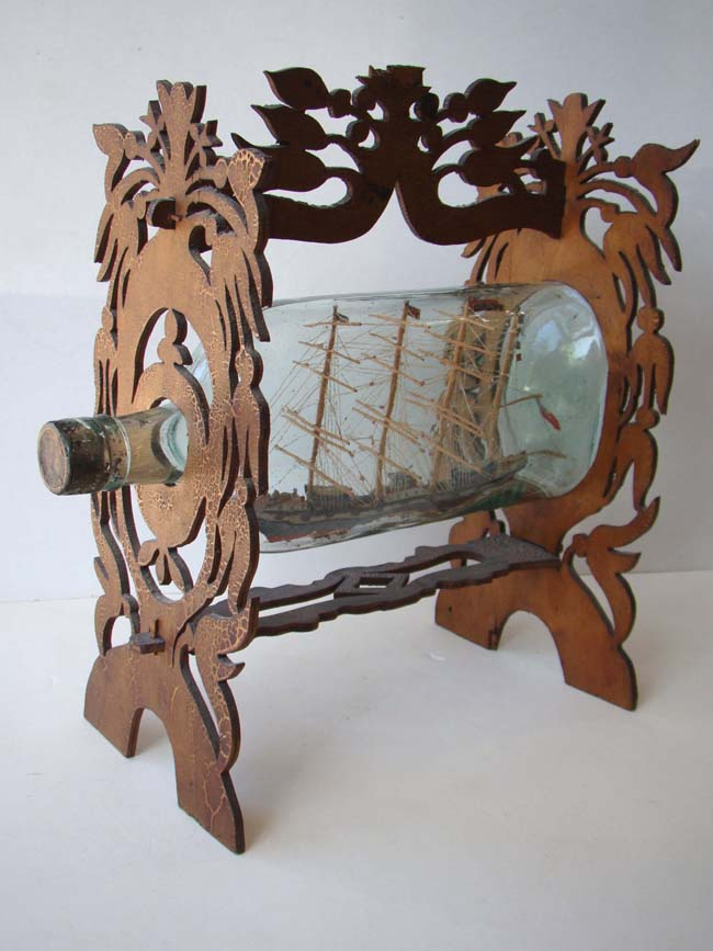click to view larger image of A fine 19th century Ship in a Bottle mounted in a carved fretwork stand circa 1880-1900