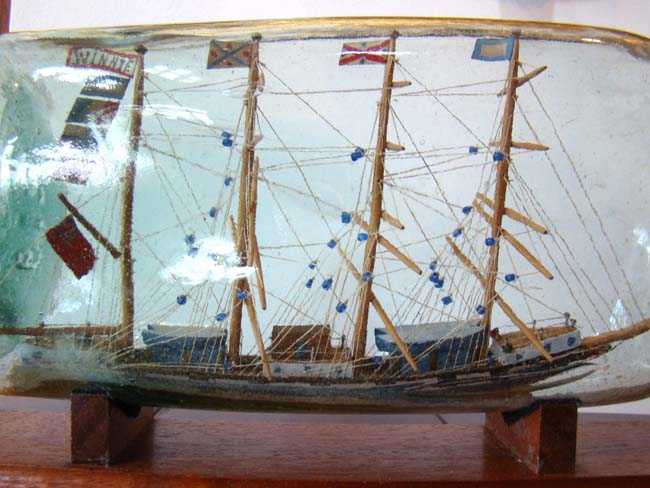 click to view larger image of A rare and large antique four-masted ship-in-a bottle circa 1880-1900