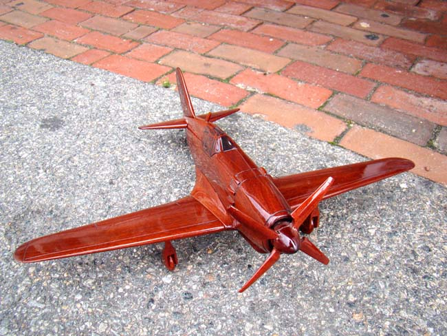 click to view larger image of A beautiful carved mahogany depiction of a World War II fighter plane, possibly a Grumman Hellcat F6F