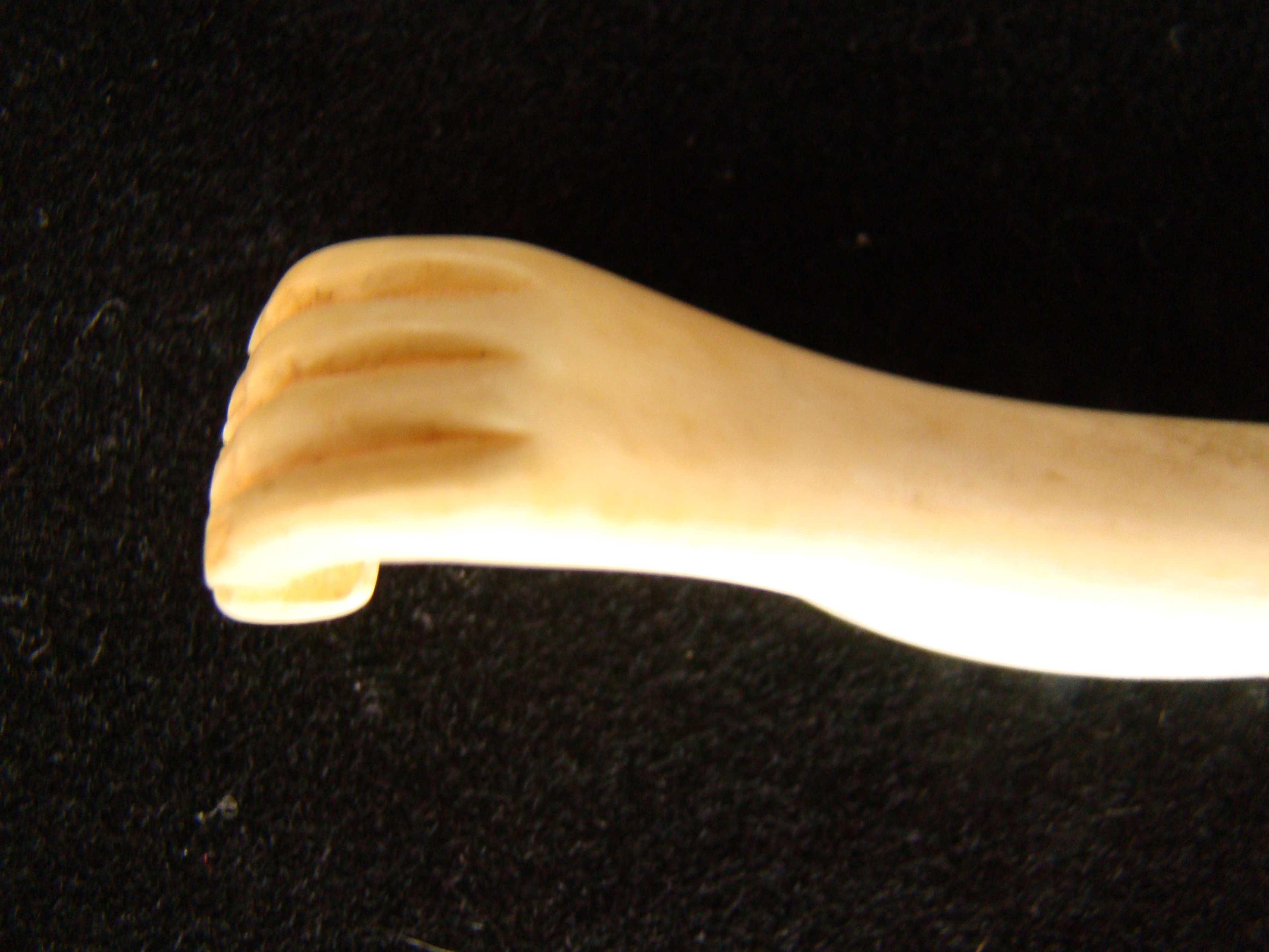 click to view larger image of A sailor -carved whale ivory bodkin depicting a hand holding a small box or book circa 1850