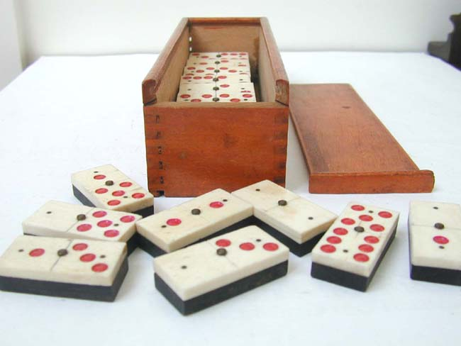 click to view larger image of An Unusual Cased Set of 24 Bone and Ebony Dominoes with Red Dots circa 1890