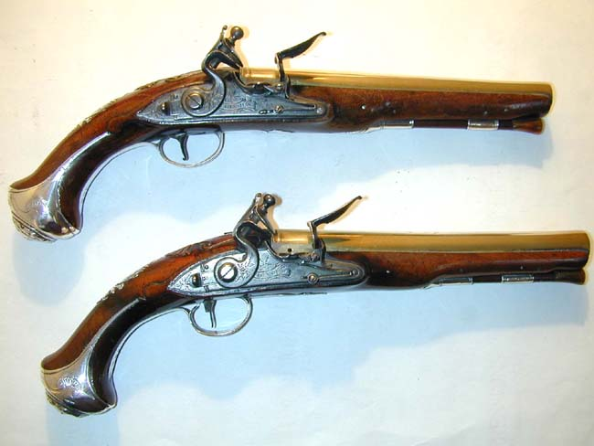 click to view larger image of A Nice Pair of Silver-Mounted Flintlock Holster Pistols with Brass Barrels signed 'J. Henshaw, London,' one hallmarked 1749, the other 1754