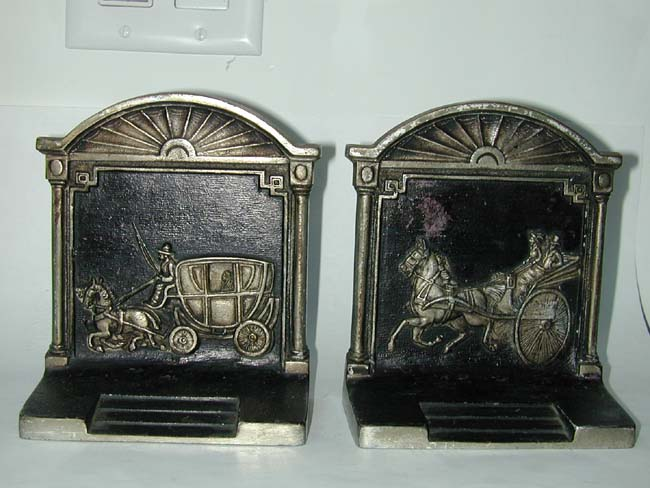 click to view larger image of A pair of Antique Bookends by Bradley & Hubbard depicting a stagecoach and a carriage.