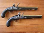 click to view detailed description of A pair of English flintlock brass barreled coaching pistols by John Bennett circa 1790