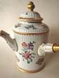 click to view detailed description of A French porcelain armorial style chocolate pot with side mounted fruitwood handle