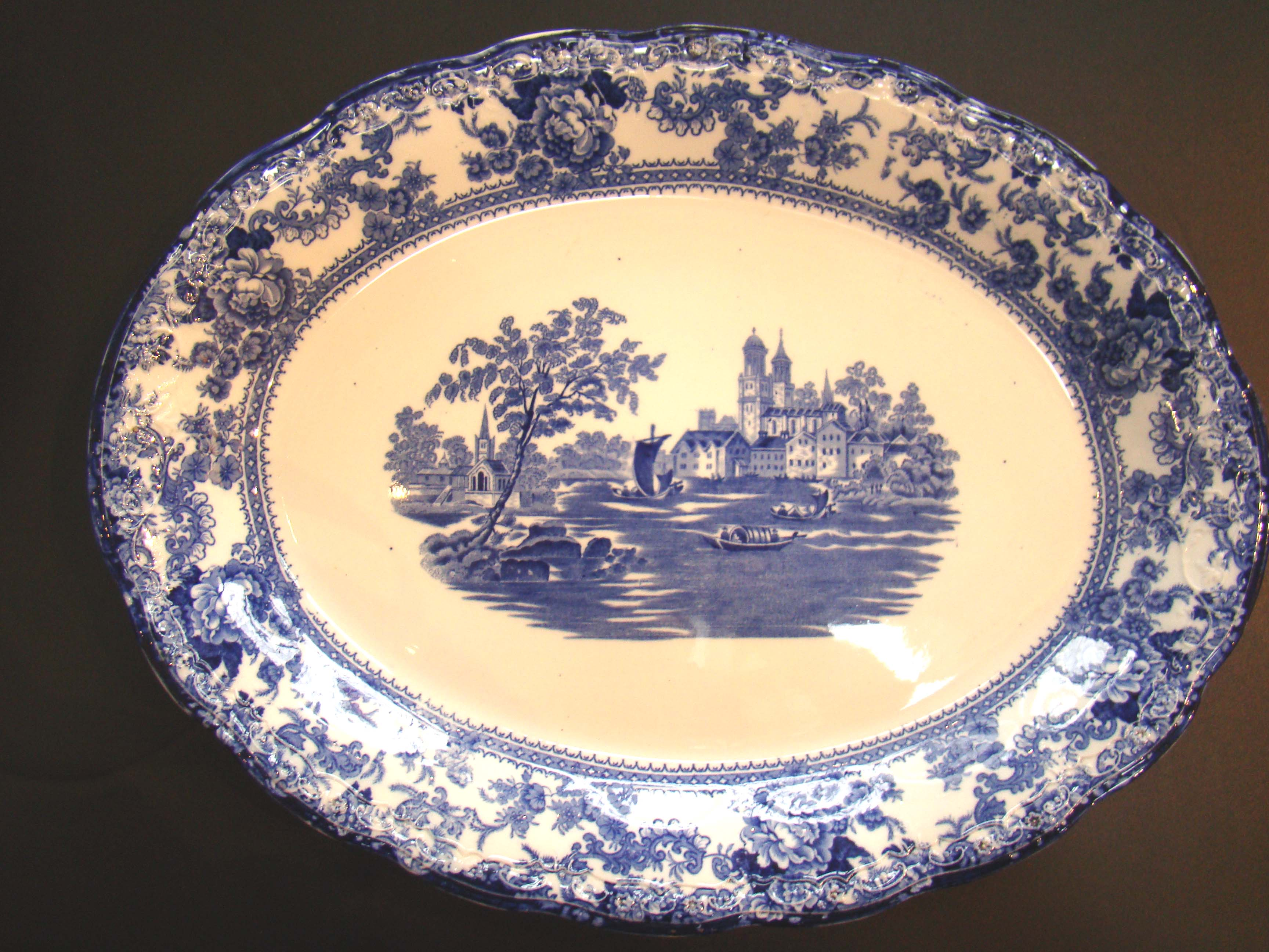 click to view detailed description of A beautiful antique flow blue serving platter by Colonial Pottery of Stoke, England, circa 1880-1900