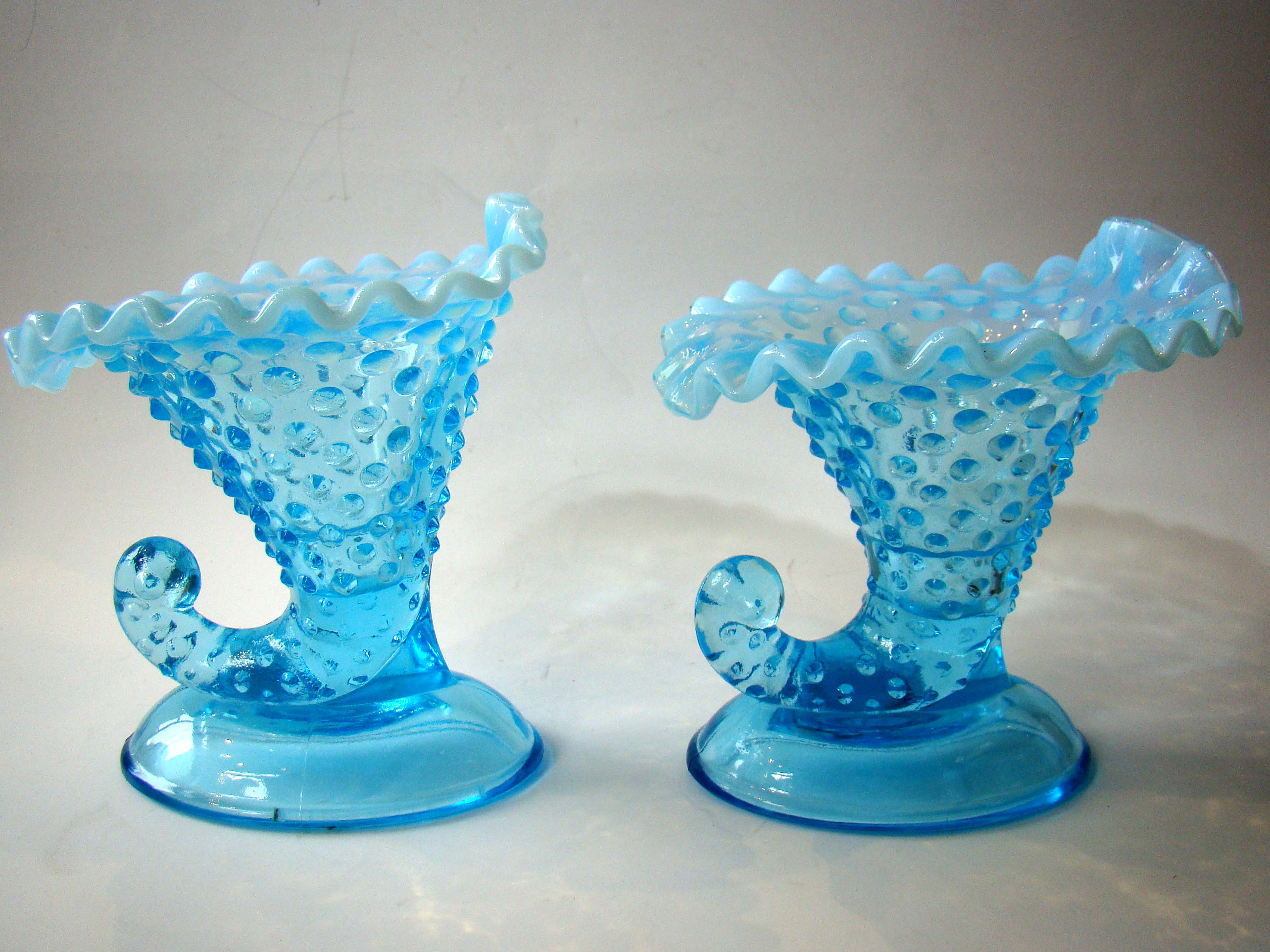 click to view detailed description of A beautiful pair of vintage aqua blue hobnail pattern cornucopia candle holders