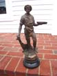 click to view detailed description of A 19th century metal sculpture of a shipbuilder holding a small ship in one hand and his tool in the other. Circa 1883.