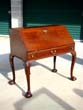 click to view detailed description of An 18th century Irish mahogany slant-front desk on cabriole legs circa 1750
