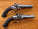 click to view detailed description of A fine pair of Double Barreled English Flintlock Coach Pistols by James Wilkinson, London, circa 1810, Gunmaker to His Majesty King George III.