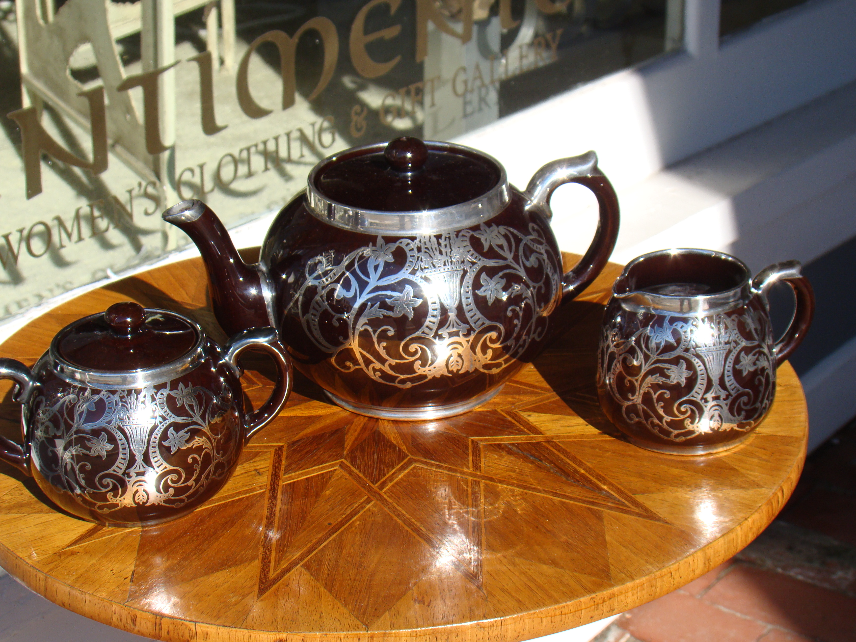 click to view detailed description of A stunning vintage Art Nouveau period silver overlay teapot, creamer and sugar by Gibsons