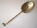 click to view detailed description of An unusual 19th century silver gilt serving spoon in the form of a branch and a leaf.
