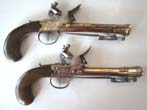 click to view detailed description of A Unique Large Pair of Unmarked, probably British, Engraved Brass Flintlock Blunderbuss Pistols with snap bayonets. Circa 1780-1800.