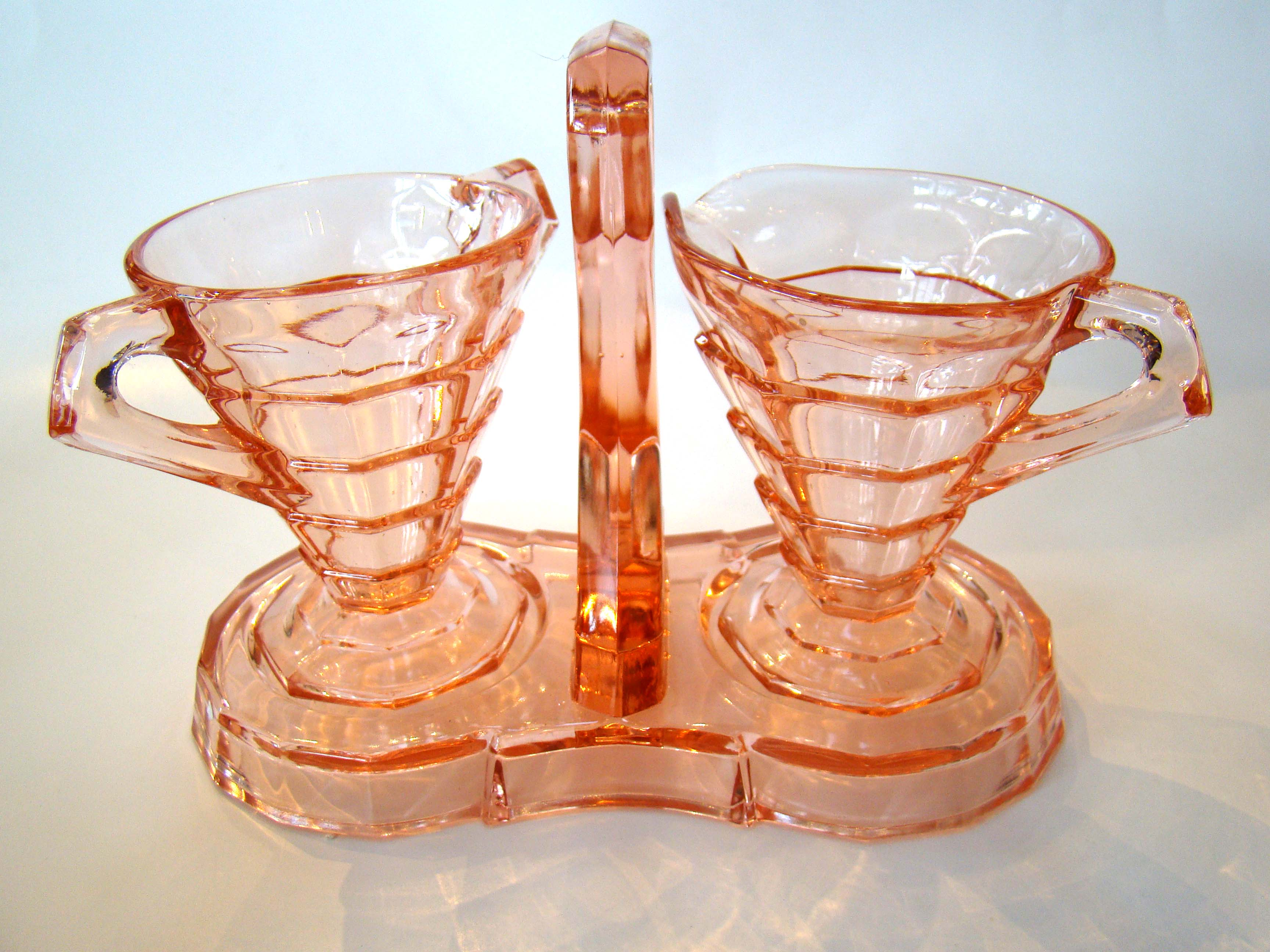 click to view detailed description of An attractive vintage pink Depression glass sugar, creamer with matching stand circa 1935