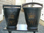 click to view detailed description of A Pair of Early 19th Century English Ducal Firebuckets Circa 1800