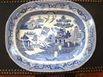 click to view detailed description of A large early 19rh century Blue Willow pattern serving platter by Lane End Pottery, circa 1830