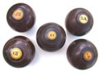 click to view detailed description of A collection of five Antique English Lignum Vitae Lawn Bowling Balls circa 1890-1920
