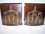 click to view detailed description of A pair of 'Lincoln in the chair' base relief bronzed bookends circa 1960