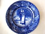 click to view detailed description of An historic souvenir plate circa 1908 depicting pilgrims John Alden and Priscilla