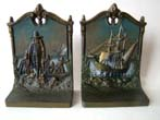 click to view detailed description of A pair of cast iron bookends circa 1930 by Bradley & Hubbard depicting the Mayflower and the Pilgrims landing at Plymouth.