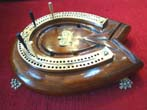 click to view detailed description of A wonderful English mahogany and brass horseshoe shaped cribbage board made circa 1890