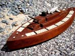 click to view detailed description of Possibly unique early 20th century bone inlaid cribbage board in the form of a Battleship with deck mounted plane.