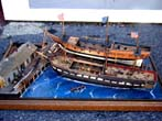 click to view detailed description of A fabulous and highly detailed scale model diorama circa 1920 of a New England Ship yard circa 1800-1812 making repairs on a 38 Gun American Frigate and a 10 Gun Privateer built circa 1785.