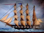 click to view detailed description of A charming miniature 19th century shadow box diorama of a four-masted ship nearing a lighthouse.