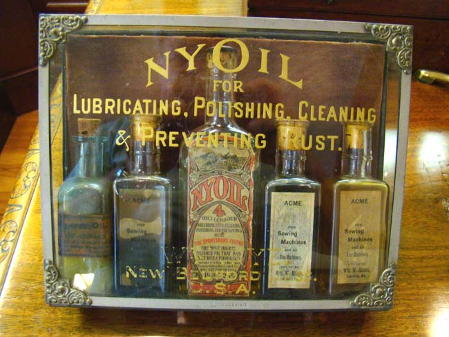 click to view detailed description of A RARE original Whale Oil display case for NYOIL containing 5 bottles circa 1890-1900