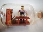 click to view detailed description of A wonderful small ship-in-a bottle depicting a sailor making a ship-in-a bottle