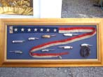 click to view detailed description of A framed collection of 8 bosuns whistles and a ships pennant
