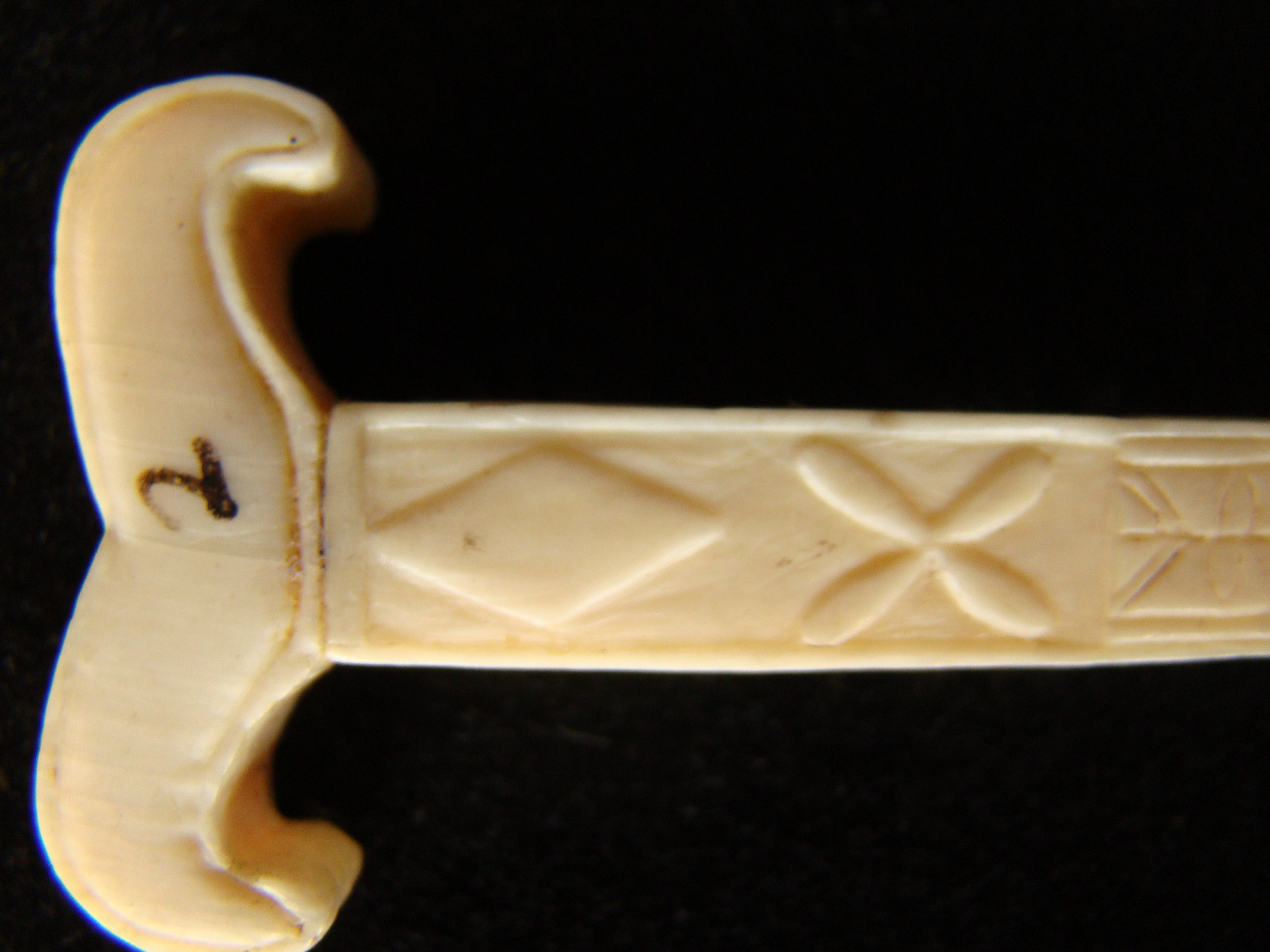 click to view detailed description of An unusual sailor-carved antique whale ivory bodkin in the form of a yoke circa 1850