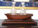 click to view detailed description of A Wonderful 19th century mahogany Decanter Stand in the form of a ship on a shipyard launching ramp circa 1850-1870.