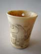 click to view detailed description of A charming 19th century scrimshawed bone cup with American eagle and the letters