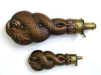 click to view detailed description of A Fine Pair of Copper Entwined Dolphin Form Powder Flasks circa 1850.