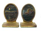 click to view detailed description of A Pair of BRADLEY & HUBBARD Antique Bookends ca. 1910 depicting a Coastal Village in the Moonlight