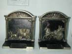 click to view detailed description of A pair of Antique Bookends by Bradley & Hubbard depicting a stagecoach and a carriage.