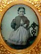 click to view detailed description of A mid 19th century Ambrotype of a Beautiful Little Girl holding a doll