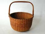 click to view detailed description of A Diminutive Nantucket Swing Handled Basket by S.P. Boyer circa 1940-1950.